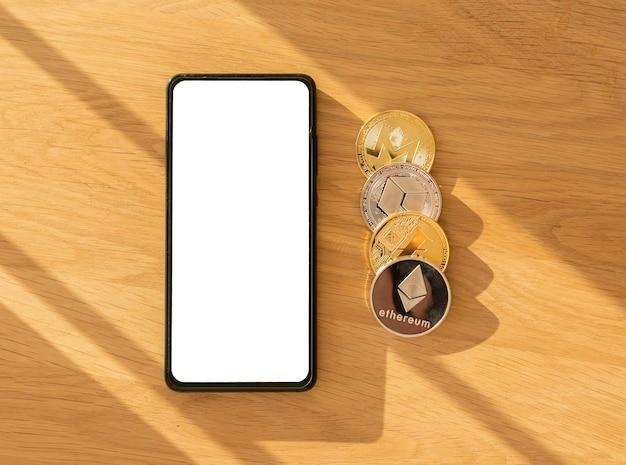 暗号通貨投資アプリケーションは、携帯電話の画面、ビットコイン、木製の背景のイーサリアムにモックアップします。