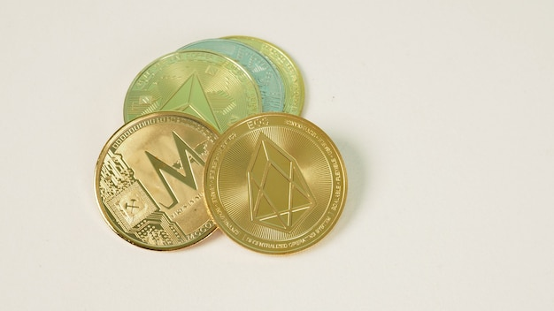 Криптовалюта с различными блестящими серебряными и золотыми монетами символа физической криптовалюты на белом фоне