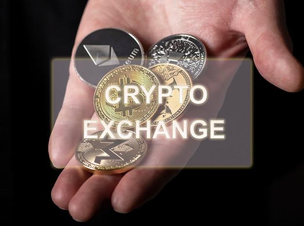 Криптообменный текст поверх рук с монетами криптовалюты