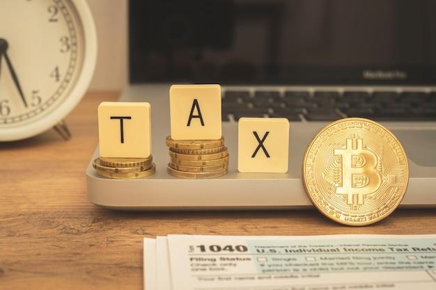 暗号課税の概念。暗号通貨でのtax日。ノートパソコン、1040アプリケーションフォーム、目覚まし時計を備えたデスクトップ