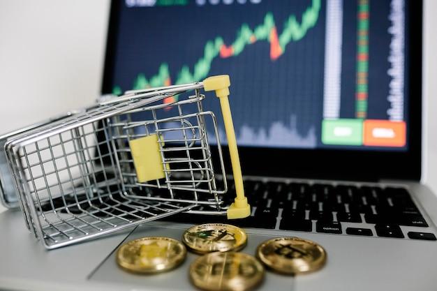 Криптовалюты и корзина или тележка на ноутбуке с графиком фондового рынка на заднем плане
