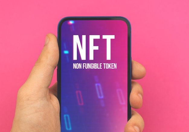 Криптовалюта и блокчейн, логотип nft на экране, мужчина держит мобильный телефон, бизнес и финансовая концепция, розовое фоновое фото