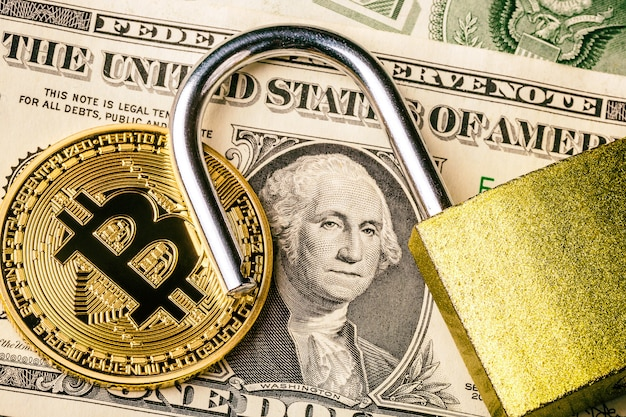 Cryptocurrency bitcoin coin near one dollar banknote and opened padlock