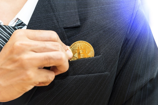 Cryptocurrency and business. businessman in black suite holding golden coin of btc. clodeup view wit