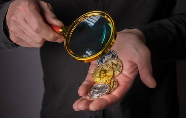 Монеты криптовалюты в мужской руке с кучей биткойнов и другой криптовалюты крупным планом