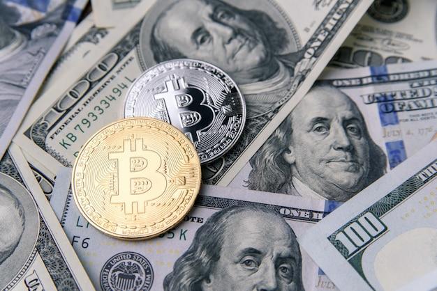 Криптовалютные монеты золотого и серебряного биткойнов на банкнотах сто долларов. виртуальные денежные вложения. криптовалюта бизнес-концепция.