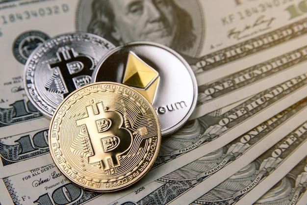 Криптовалютные монеты золотого, серебряного биткойна и эфириума на банкнотах по сто долларов. виртуальные денежные вложения. криптовалюта бизнес-концепция.