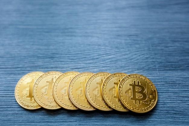 Криптовалюта золотой биткойн, биткойн-монеты на деревянном фоне, концепция добычи биткойнов