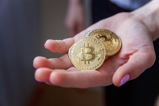 여자 손에 cryptocurrency 황금 bitcoin 동전입니다. 웹 뱅킹 및 국제 네트워크 결제를 위한 전자 가상 화폐. 암호 화폐의 상징.