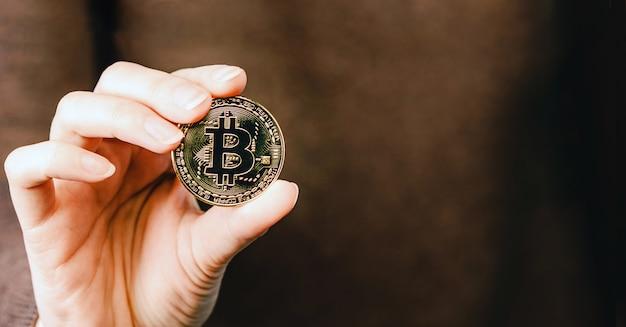 Золотая монета биткойн криптовалюты. мужчина держит в руке символ криптовалюты - электронные виртуальные деньги для веб-банкинга и международных сетевых платежей, выборочный фокус, тонированные