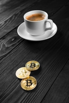 Cryptocurrency golden bitcoin standing on coffee cup isolated on a wood background