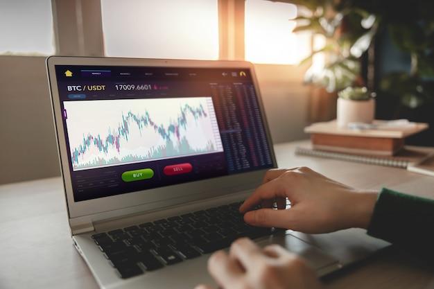 暗号通貨投資の概念。オンライン交換プラットフォームを介してビットコインを売買するために自宅でコンピューターのラップトップを使用している人。ブロックチェーン、フィンテックテクノロジー。金融投資の革新