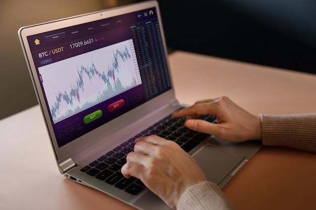 暗号通貨投資の概念。自宅でコンピューターのラップトップを使用して、オンライン取引所プラットフォームを介してビットコインを売買する人。ブロックチェーン、フィンテックテクノロジー。金融投資の革新