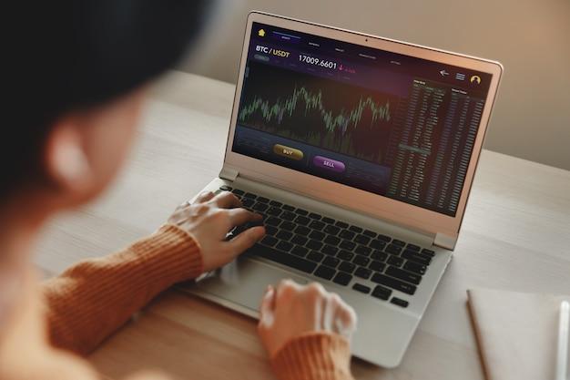 自宅でコンピューターのラップトップを使用してビットコインを売買する暗号通貨投資コンセプトの人
