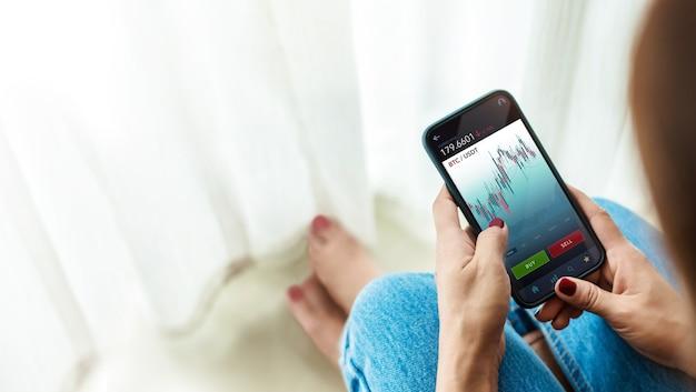 暗号通貨投資の概念。自宅で携帯電話を使用してオンライン取引所プラットフォームを介してビットコインを売買する人。 blockhain、フィンテックテクノロジー。金融投資の革新