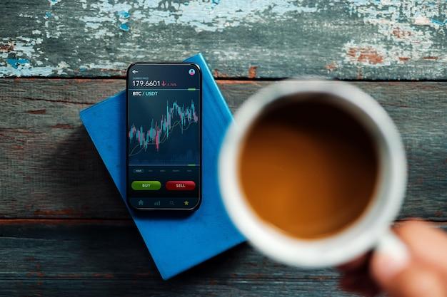 自宅で携帯電話を使用してビットコインを売買する暗号通貨投資コンセプトの人