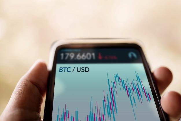 暗号通貨投資の概念。オンライン取引所プラットフォームを介してビットコインを売買するために携帯電話を使用している人。ブロックチェーン、フィンテックテクノロジー。金融投資の革新。クローズアップショット