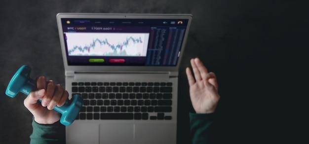Cryptocurrency 투자 개념입니다. 컴퓨터 노트북을 사용하여 bitcoin을 거래하는 동안 명상 요가를 하고 아령으로 운동하는 여성. 블록체인, 핀테크 기술