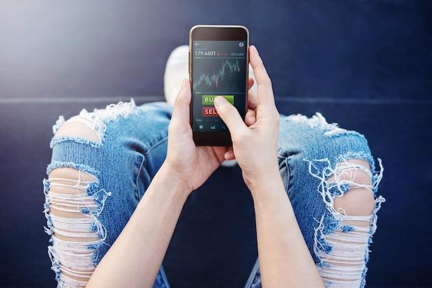暗号通貨投資コンセプト屋外で携帯電話を使用してビットコインを売買する若い女性