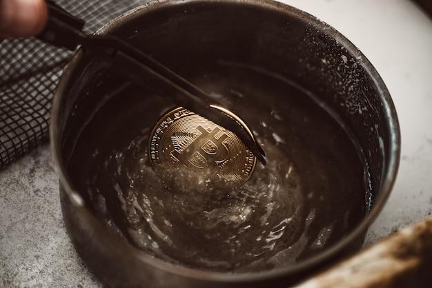 암호화폐 시장이 끓고 있습니다. 작업장에서 물 냄비에 끓는 비트코인의 클로즈업 보기