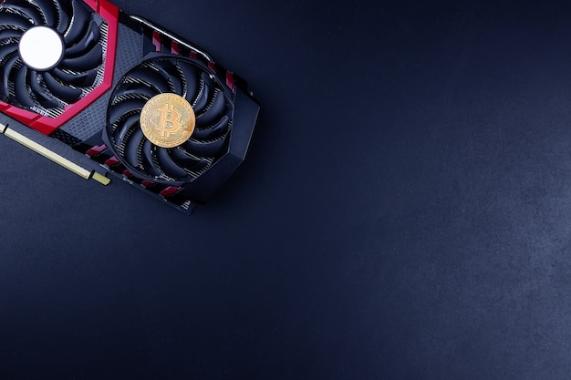 Cryptocurrency mining concept with golden bitcoin coins next to a computer performant video card black background