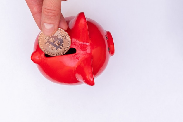 Cryptocurrency saving concept. hand puts a bitcoin coin in a red piggy bank on a white background, top view, close-up, copy space. electronic digital money accumulation concept.