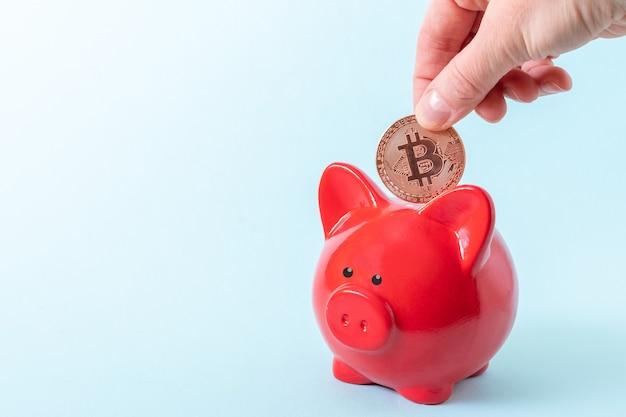 Cryptocurrency 저축 개념. 손을 파란색 배경에 빨간 돼지 저금통 위에 bitcoin 동전을 보유합니다.