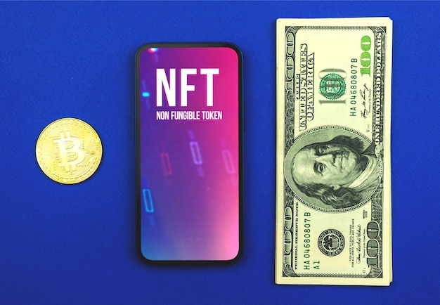 Криптографический nft, логотип невзаимозаменяемого токена на экране современного мобильного телефона, офисный синий стол с деньгами и крипто-биткойнами, концепция криптовалюты и технологий, фото вида сверху