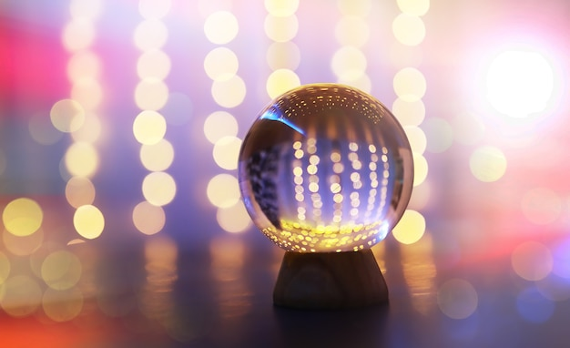 Crystal ball on the floor with bokeh, lights behind. glass ball with colorful bokeh light, celebration concept.