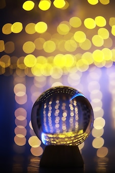 Crystal ball on the floor with bokeh, lights behind. glass ball with colorful bokeh light, new year celebration concept.