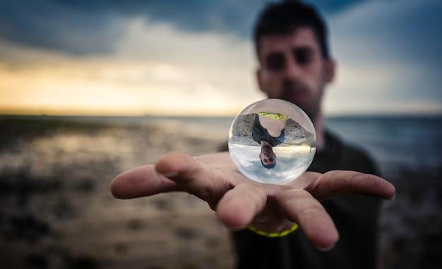 Crystal ball over the hand on the beach
