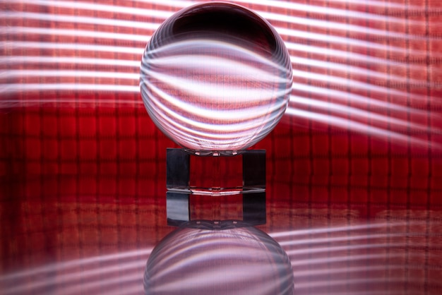 Crystal ball reflecting a red background with lights around it, light painting, selective focus.