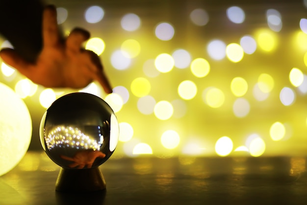Crystal ball on the table with bokeh, lights behind. glass ball with colorful bokeh light, prediction concept.