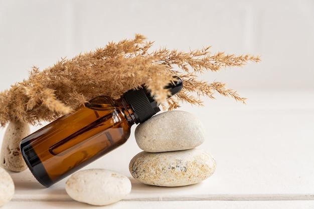 健康的なスキンケアのためのエッセンシャルオイルが入ったクリスタルスポイトボトル。自然な化粧品と実質的なエコパッケージのコンセプト。