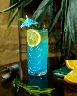 A crystal glass of blue lagoon garnished with lemon slice and cocktail umbrella