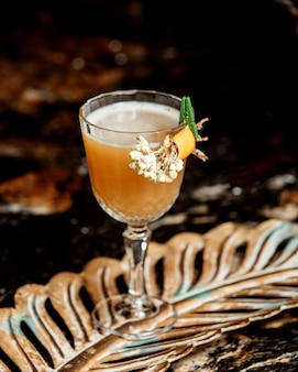 Crystal glass of cocktail garnished with flower and orange zest
