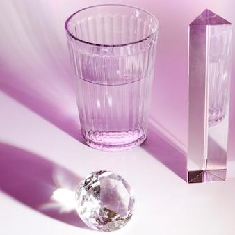 물의 크리스탈 유리; 프리즘과 분홍색 배경에 빛나는 다이아몬드