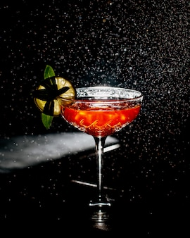 A crystal glass of orange cocktail garnished with lime slice in dark background with light