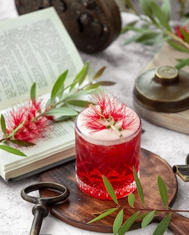 Crystal glass of red cocktail garnished with flower