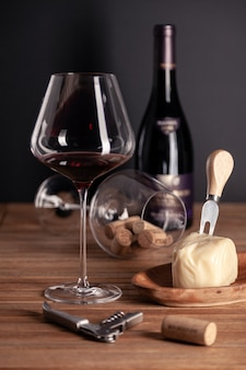 Crystal glass of red wine, bottles, corkscrew, decanter, cheese, corks on wooden table