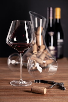 Crystal glass of red wine, bottles, corkscrew, decanter, corks on wooden table