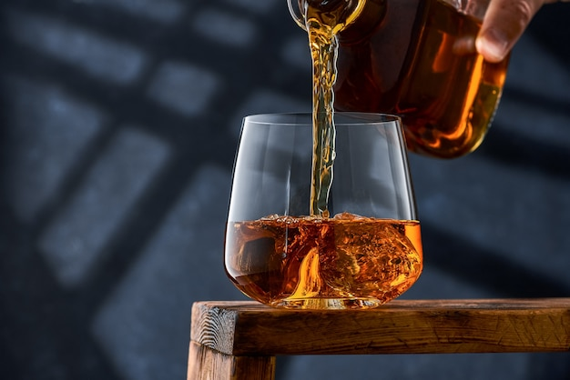 Crystal glass of whiskey with ice on a wooden counter