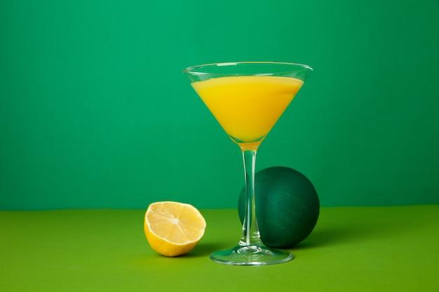 Хрустальный бокал со свежим алкогольным напитком, который подается на столе рядом с сочным разрезанным пополам лимоном и декоративным шаром на зеленом фоне