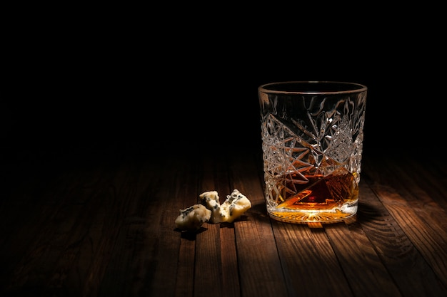 Crystal glass with whiskey and snacks on a wooden table on a black background