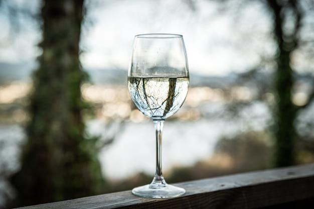 Хрустальный бокал с белым вином на деревянных перилах на террасе дома, расположенного на природе