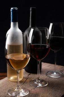 Хрустальные бокалы с красным и белым вином и винными бутылками, над деревянным столом