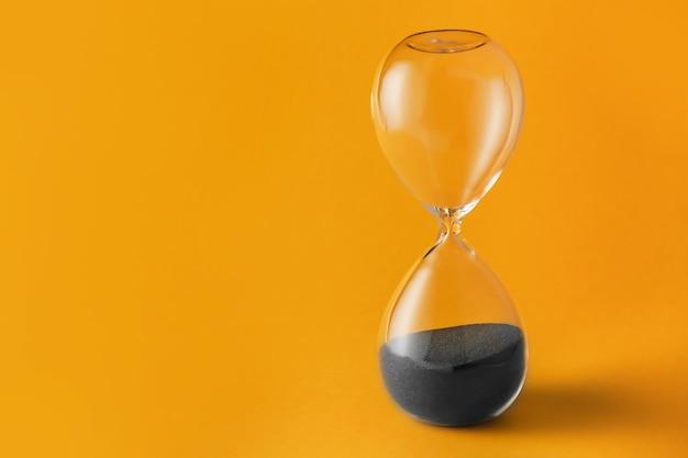 Хрустальные песочные часы на цветном фоне