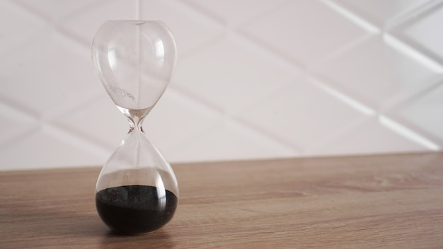 Хрустальные песочные часы с черным песком на деревянном столе и белом фоне Premium Фотографии