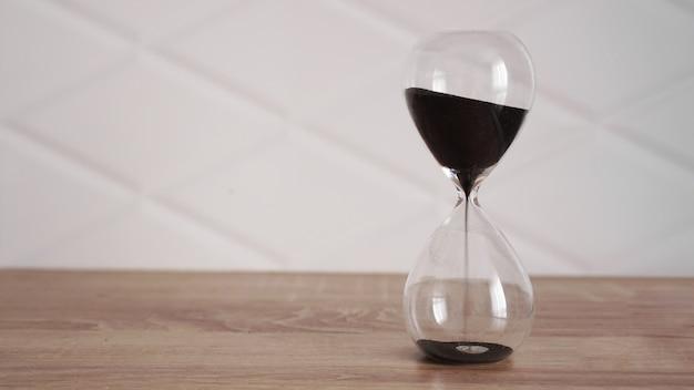 Хрустальные песочные часы с черным песком на деревянном столе и белом фоне
