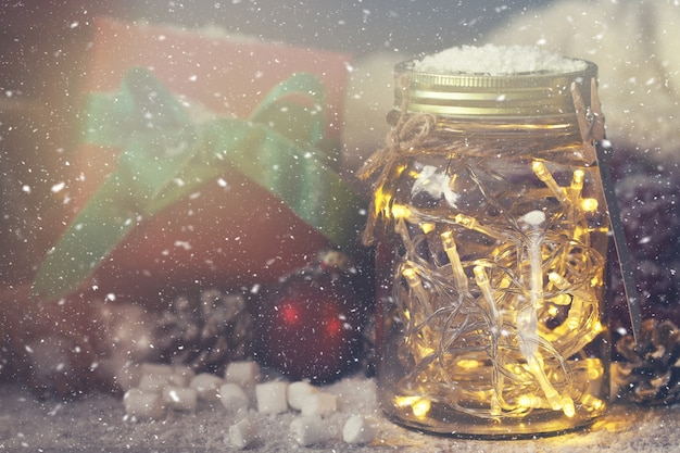 Crystal jar with lights with a gift next to it while it snows Free Photo